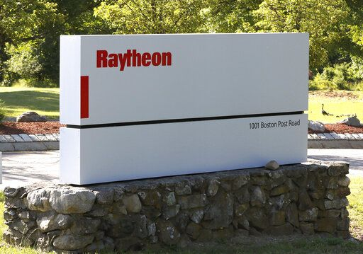 A sign stands at the road leading to the Raytheon facility Monday, June 10, 2019, in Marlborough, Mass. Raytheon Co. and United Technologies Corp. are merging in a deal that creates one of the world's largest defense companies.