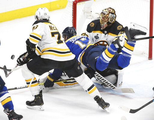 St. Louis Blues left wing Jaden Schwartz (17) falls between Boston Bruins goaltender Tuukka Rask, of Finland, right, and defenseman Charlie McAvoy (73) during the second period of Game 6 of the NHL hockey Stanley Cup Final Sunday, June 9, 2019, in St. Louis.
