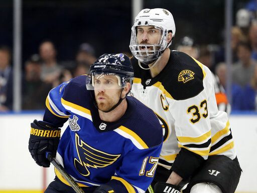 Boston Bruins defenseman Zdeno Chara (33), of Slovakia, wears a mask to protect his injured jaw as he and St. Louis Blues left wing Jaden Schwartz (17) play during the second period of Game 6 of the NHL hockey Stanley Cup Final Sunday, June 9, 2019, in St. Louis.