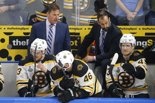 Boston Bruins head coach Bruce Cassidy, top left, watches the action during the first period of Game 6 of the NHL hockey Stanley Cup Final between the Bruins and the St. Louis Blues Sunday, June 9, 2019, in St. Louis.