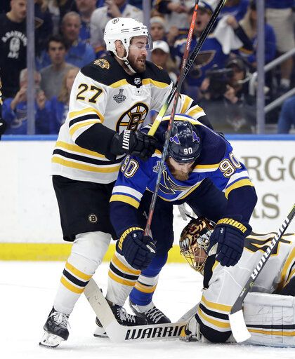St. Louis Blues center Ryan O'Reilly (90) falls between Boston Bruins defenseman John Moore (27) and goaltender Tuukka Rask (40), of Finland, during the second period of Game 6 of the NHL hockey Stanley Cup Final Sunday, June 9, 2019, in St. Louis.