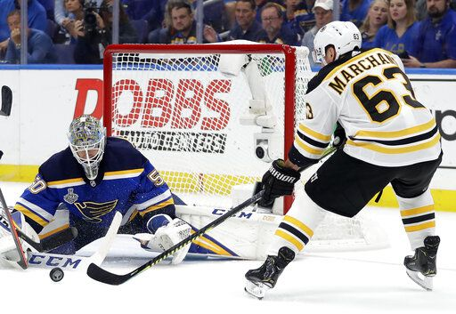 Boston Bruins left wing Brad Marchand (63) reaches for a rebound in front of St. Louis Blues goaltender Jordan Binnington (50) during the first period of Game 6 of the NHL hockey Stanley Cup Final Sunday, June 9, 2019, in St. Louis.