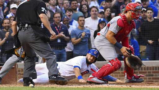 Chicago Cubs' David Bote, center, scores past St. Louis Cardinals catcher Andrew Knizner, right, during the fifth inning of a baseball game Sunday, June 9, 2019, in Chicago.