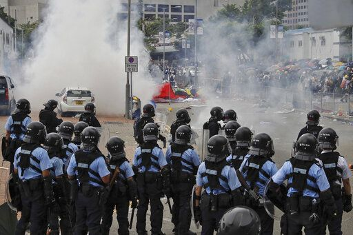 Protesters run away from riot police firing tear gas outside the Legislative Council during a massive demonstration in Hong Kong, Wednesday, June 12, 2019. Hong Kong police have used tear gas and high-pressure hoses against thousands of protesters opposing a highly controversial extradition bill outside government headquarters.