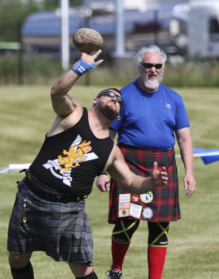 Daniel Verstat of Lisle threw in the open stone Braemar Stone competition as Rick Kramer, right, of Villa Park, waited his turn at a previous Scottish Festival and Highland Games in Itasca.