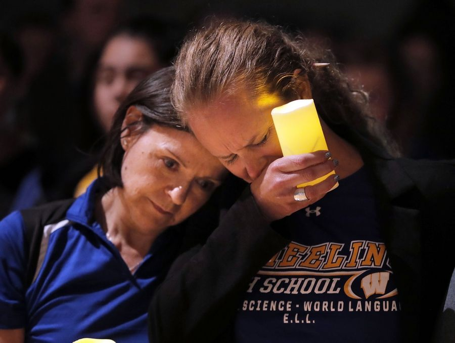 Wheeling High School teachers Sandra Chico, left, and Rebecca Castro weep during a vigil for retired Wheeling High teacher Anne Martin and her husband, David, who were killed in their Arlington Heights home Saturday.