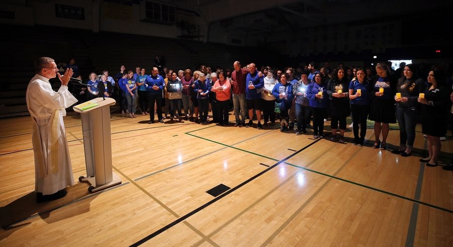 Deacon Tom Westerkamp of St. James Catholic Church in Arlington Heights leads a prayer vigil in the gymnasium at Wheeling High School for retired Wheeling High School teacher Anne Martin and her husband, David, who were killed in their Arlington Heights home Saturday.