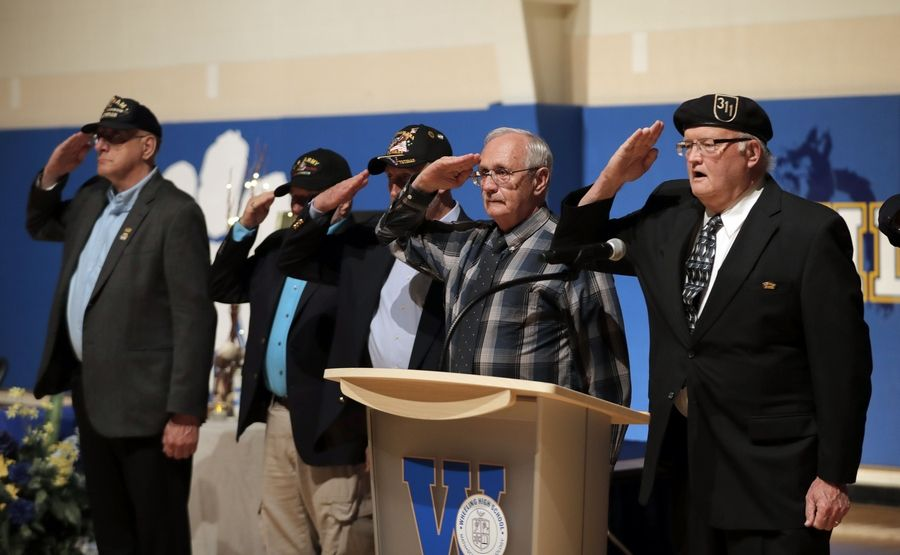 Veterans salute David Martin, a Vietnam veteran, as people gather in the gymnasium at Wheeling High School during a vigil for Martin and his wife, Anne.