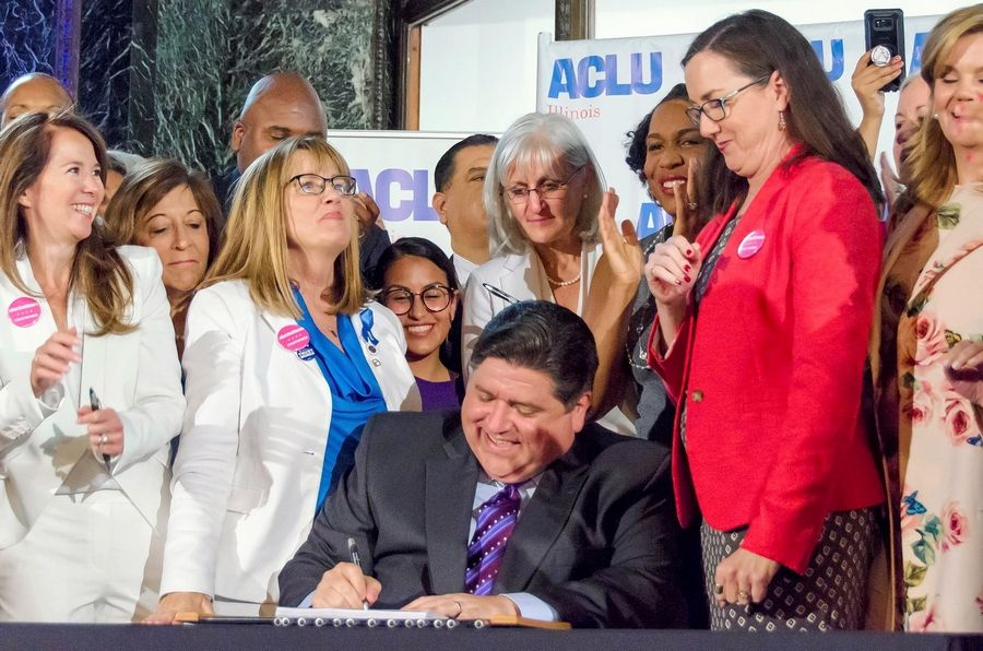 Gov. J.B. Pritzker signs into law the Reproductive Health Act during a ceremony Wednesday at the Chicago Cultural Center, accompanied by the bill's sponsors, Sen. Melinda Bush, D-Grayslake, left, and Rep. Kelly Cassidy, D-Chicago.