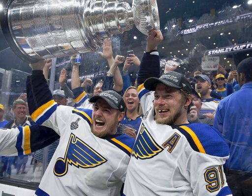 St. Louis Blues' Ivan Barbashev, left, and Vladimir Tarasenko, both of Russia, hold the Stanley Cup as fans in the stands celebrate after the Blues defeated the Boston Bruins in Game 7 of the NHL Stanley Cup Final, Wednesday, June 12, 2019, in Boston.