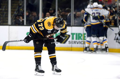 Boston Bruins' Charlie McAvoy reacts as the St. Louis Blues' celebrate Brayden Schenn's goal, right, during the third period in Game 7 of the NHL hockey Stanley Cup Final, Wednesday, June 12, 2019, in Boston.