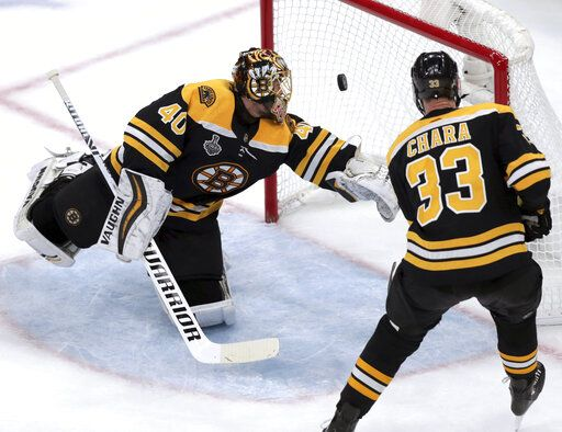 The puck bounces off the post behind Boston Bruins goaltender Tuukka Rask, left, of Finland, and Zdeno Chara, right, of Slovakia, during the second period in Game 7 of the NHL hockey Stanley Cup Final against the St. Louis Blues, Wednesday, June 12, 2019, in Boston.