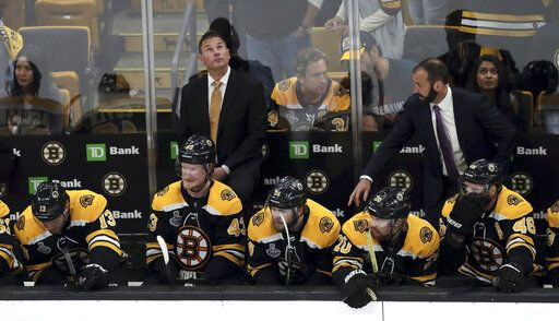 Boston Bruins head coach Bruce Cassidy checks the clock as time winds down during the third period in Game 7 of the NHL hockey Stanley Cup Final against the St. Louis Blues, Wednesday, June 12, 2019, in Boston.