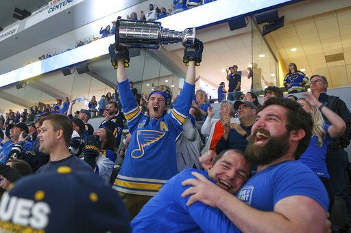A St. Louis Blues fan at a hoists a replica Stanley Cup in celebration at a watch party in the Enterprise Center in St. Louis after the Blues scored a goal during the first period of Game 7 of the NHL hockey Stanley Cup Final against the Boston Bruins in Boston.
