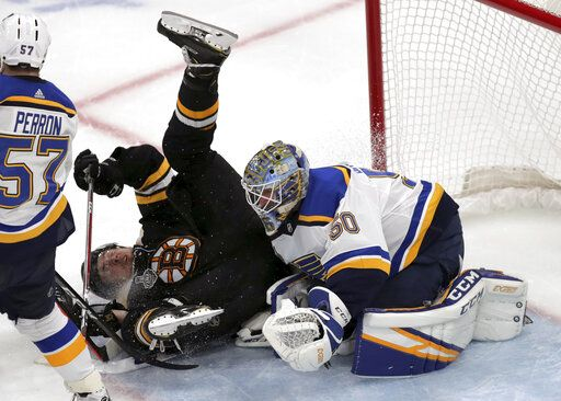 Boston Bruins' Charlie McAvoy, left, crashes to the ice in front of St. Louis Blues goaltender Jordan Binnington during the third period in Game 7 of the NHL hockey Stanley Cup Final, Wednesday, June 12, 2019, in Boston.