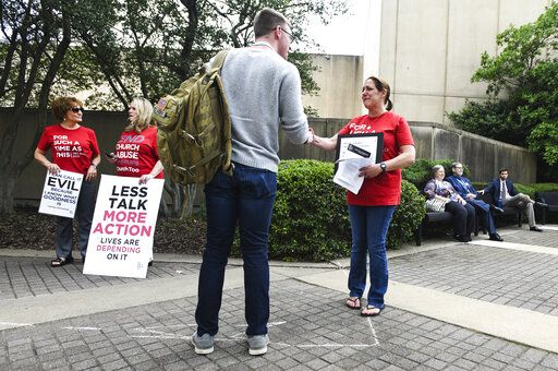 Jules Woodson, right, of Colorado Springs, Colo., hands out flyers while demonstrating outside the Southern Baptist Convention's annual meeting Tuesday, June 11, 2019, in Birmingham, Ala. First-time attendee Woodson spoke through tears as she described being abused sexually by a Southern Baptist minister.