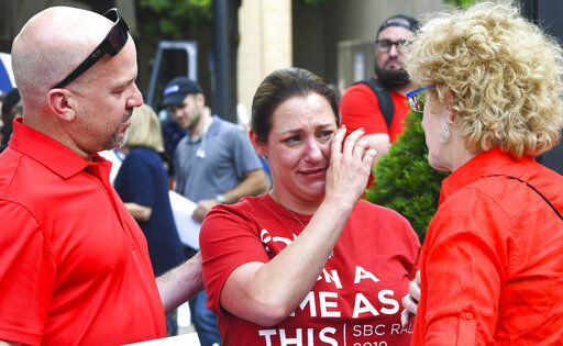 Jules Woodson, center, of Colorado Springs, Colo., is comforted by her boyfriend Ben Smith, left, and Christa Brown while demonstrating outside the Southern Baptist Convention's annual meeting Tuesday, June 11, 2019, in Birmingham, Ala. First-time attendee Woodson spoke through tears as she described being abused sexually by a Southern Baptist minister.