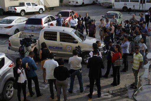 Journalists surround the police vehicle carrying Eddy Vladimir Féliz Garcia who was taken into custody in connection with the shooting of former Boston Red Sox slugger David Ortiz, as he is taken to court in Santo Domingo, Dominican Republic, Tuesday, June 11, 2019. His lawyer, Deivi Solano, said Féliz Garcia had no idea who he'd picked up and what was about to happen, and that he expected Féliz Garcia would be charged as an accomplice to an attempted murder.