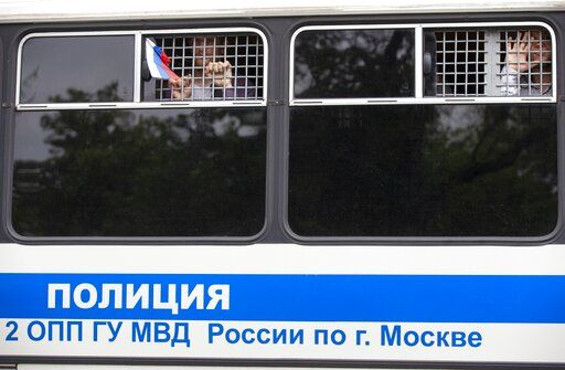 Detained protesters look out of a police bus window during a march in Moscow, Russia, Wednesday, June 12, 2019. Police and hundreds of demonstrators are facing off in central Moscow at an unauthorized march against police abuse in the wake of the high-profile detention of a Russian journalist. More than 20 demonstrators have been detained, according to monitoring group.