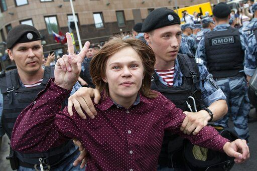 Police officers detain a young protester during a march in Moscow, Russia, Wednesday, June 12, 2019. Police and hundreds of demonstrators are facing off in central Moscow at an unauthorized march against police abuse in the wake of the high-profile detention of a Russian journalist. More than 20 demonstrators have been detained, according to monitoring group.
