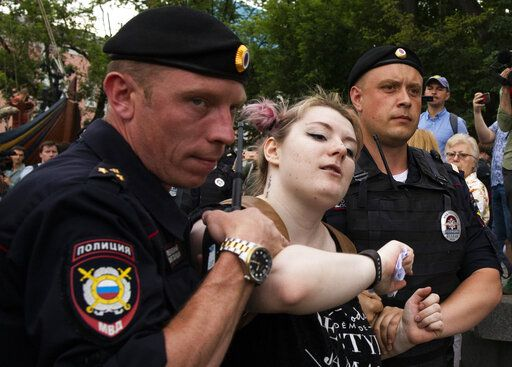Police officers detain a woman during a march in Moscow, Russia, Wednesday, June 12, 2019. Police and hundreds of demonstrators are facing off in central Moscow at an unauthorized march against police abuse in the wake of the high-profile detention of a Russian journalist. More than 20 demonstrators have been detained, according to monitoring group.