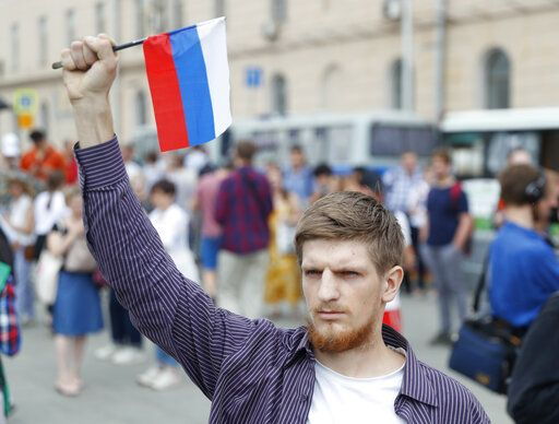Young mans holds a state flag as supporters of Russian investigative journalist Ivan Golunov and other protesters gather to attend a march in Moscow, Russia, Wednesday, June 12, 2019.