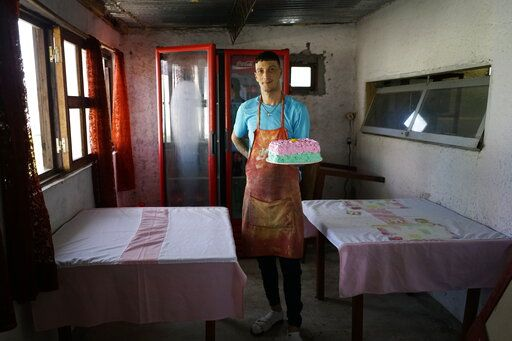 In this May 18, 2019 photo, inmate Nelson Avantti, who runs a bakery inside the Punta de Rieles prison, holds a cake at his bakery at the prison in Montevideo, Uruguay. Money to start businesses like Avantti's comes from inmates' families or from a quasi-bank largely administered by inmates themselves.