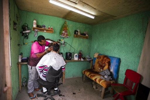 In this May 9, 2019 photo, an inmate at the Punta de Rieles prison that runs one of the existing barbershops, cuts the hair of another inmates t the prison in Montevideo, Uruguay. To get chosen for Punta de Rieles, prisoners have to have at least a six-month period of good behavior elsewhere.
