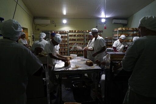 In this May 15, 2019 photo, inmates work at a bakery at the Punta de Rieles prison, in Montevideo, Uruguay. This bakery was started by two prisoners who have kept it going despite being released and now employ 50 to 70 people.