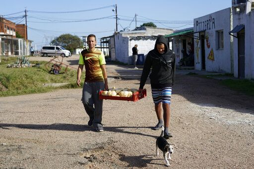 In this May 15, 2019 photo, inmates carry bread to their cells at the Punta de Rieles prison in Montevideo, Uruguay. The bakery is run by former inmates that come back to the prison almost daily and sometimes even sleep there, voluntarily this time.