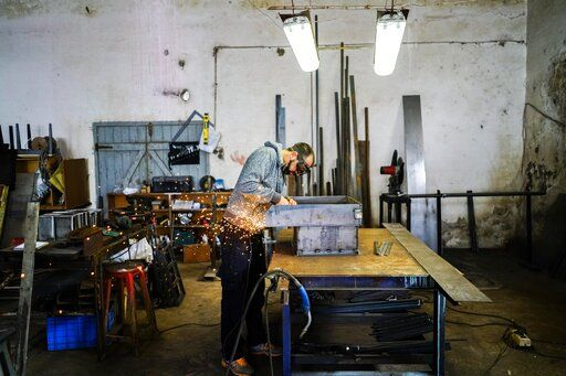 In this May 20, 2019 photo, former inmate Mauro Rodríguez works at the blacksmith shop at the Punta de Rieles prison in Montevideo, Uruguay. Rodríguez came to repair a machine that makes cement blocks, that he'd created while spending several years as an inmate. He now has a blacksmith's shop on the outskirts of Montevideo, where he works with his brother.