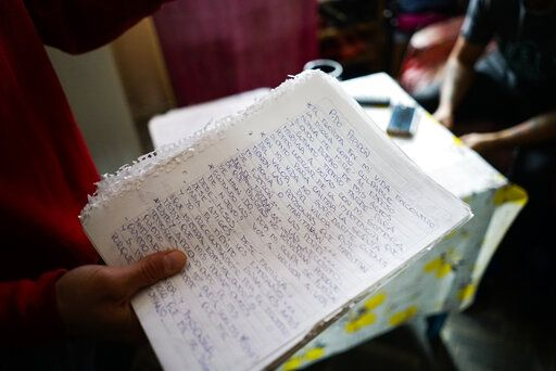 In this May 29, 2019 photo, inmate Federico Gonzalez, also known as Kung-Fu OmBijam, holds his handwritten lyrics inside his cell at the Punta de Rieles prison in Montevideo, Uruguay. Federico is a well known rap singer who is usually allowed to perform outside the prison.