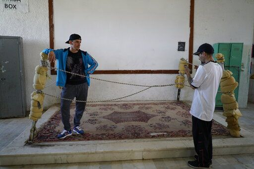 In this May 15, 2019 photo, inmate Federico Gonzalez, a musician also known as Kung-Fu OmBijam, talks to another inmate, a rap singer known as MC Mafia, at a multipurpose hall inside the Punta de Rieles prison in Montevideo, Uruguay. Gonzalez has been authorized to go outside the prison to develop cultural or educational activities, having been allowed the leave the prison grounds more than 250 times.