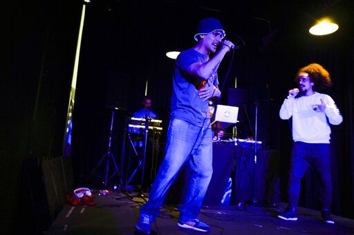 In this May 11, 2019 photo, inmate Federico Gonzalez, left, a musician also known as Kung-Fu OmBijam, performs at La Cretina pub during a Hip Hop festival in Montevideo, Uruguay, Wednesday, May 15, 2019. Gonzalez is an inmate at the Punta de Rieles prison in Montevideo, but is allowed to leave the grounds to perform as part of a program designed to rehabilitate the inmates of the prison.