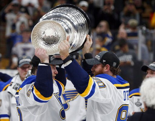 St. Louis Blues' Ryan O'Reilly, right, hands the Stanley Cup to Vladimir Tarasenko, left, of Russia, after the Blues defeated the Boston Bruins in Game 7 of the NHL Stanley Cup Final, Wednesday, June 12, 2019, in Boston.