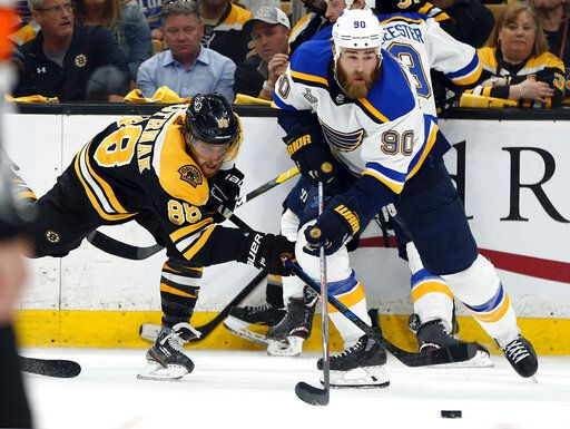 St. Louis Blues' Ryan O'Reilly (90) moves the puck away from Boston Bruins' David Pastrnak, left, of the Czech Republic, during the second period in Game 7 of the NHL hockey Stanley Cup Final, Wednesday, June 12, 2019, in Boston.