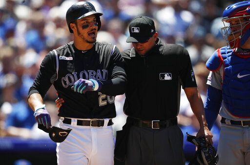 Colorado Rockies' Nolan Arenado, left, reacts after getting hit by a pitch from Chicago Cubs starting pitcher Cole Hamels as home plate umpire Roberto Ortiz and catcher Victor Caratini look on in the third inning of a baseball game Wednesday, June 12, 2019, in Denver.