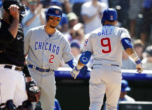 Chicago Cubs' Carlos Gonzalez, left, congratulates Javier Baez as he returns to the dugout after hitting a two-run home run off Colorado Rockies relief pitcher Phillip Diehl in the eighth inning of a baseball game Wednesday, June 12, 2019, in Denver.