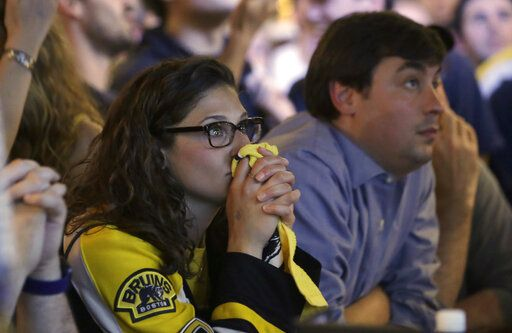 A Boston Bruins fan, left, clasps her hands together while watching television coverage of Game 7 of the NHL hockey Stanley Cup Final between the Bruins and the St. Louis Blues in a bar, Wednesday, June 12, 2019, in Boston.