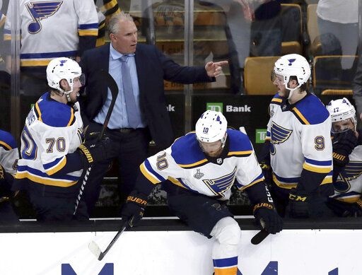 St. Louis Blues head coach Craig Berube, rear, gives his team instructions from behind the bench during the second period in Game 7 of the NHL hockey Stanley Cup Final against the Boston Bruins, Wednesday, June 12, 2019, in Boston.