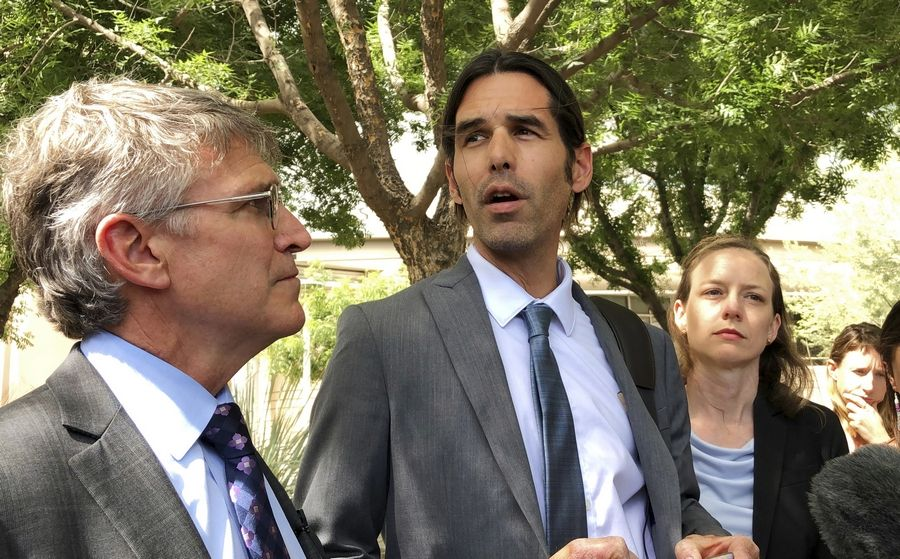 Scott Warren, center, speaks outside federal court, Tuesday, June 11, 2019. in Tucson, Ariz., after a mistrial was declared in the federal case against him. The jury announced it was deadlocked in the case against Warren, a border activist charged with conspiracy to transport and harbor migrants, in a trial that humanitarian aid groups said would have wide implications on their work.