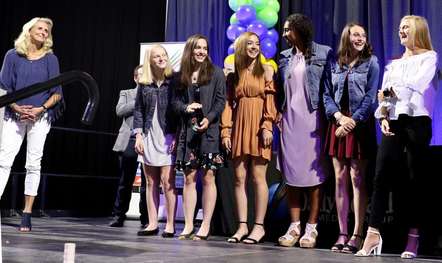 Coach Kim deMarigny, left, and members of the Class 4A state champion Maine West girls basketball team gather on stage during the Daily Herald Prep Sports Excellence Awards at Sears Centre Arena in Hoffman Estates on Thursday night. The team was awarded a Sweet Moments Award at the event.
