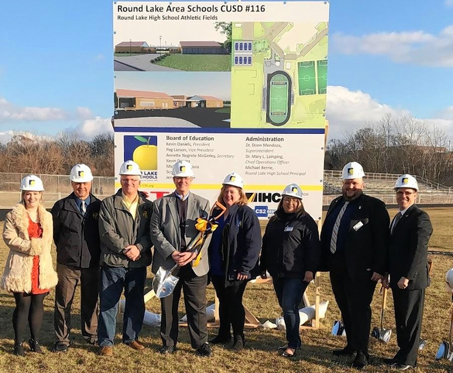 Members of the Round Lake Area Unit School District 116 school board and administration pose in front of the site of the district's $7 million athletic fields project at Round Lake High School.