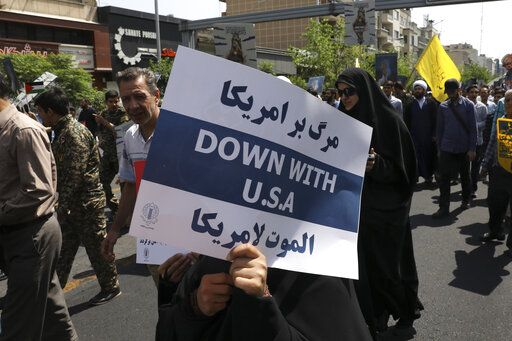 FILE - In this May 31, 2019 file photo, a demonstrator holds an anti-U.S. placard during the annual Quds, or Jerusalem Day rally in Tehran, Iran. The top line on the placard in Farsi translates to, Death to America, and the bottom line on the placard in Arabic translates to, Death to America.