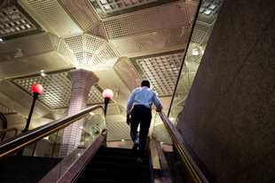A man climes the escalator of the Wall Street subway station near the New York Stock Exchange on Sept. 17, 2018.