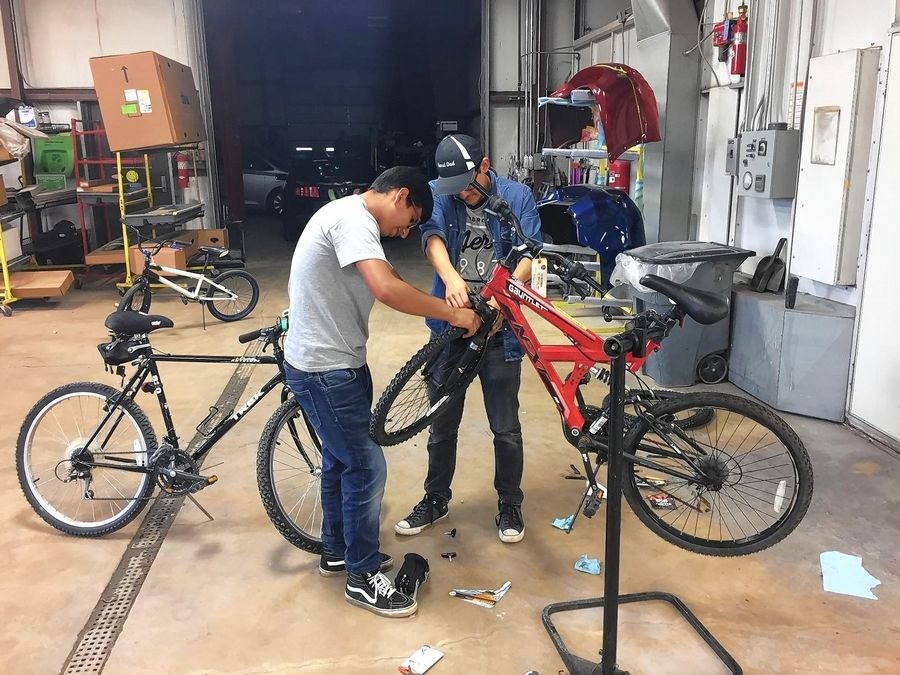 Marcos Escobar, left, and Saul Torres work on a donated bike during a workshop event at Collision Solution in Hainesville Thursday evening.