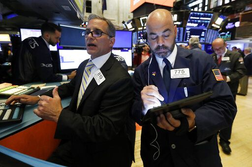 FILE - In this June 6, 2019, file photo specialist Anthony Rinaldi, left, and trader Fred DeMarco work on the floor of the New York Stock Exchange. The U.S. stock market opens at 9:30 a.m. EDT on Friday, June 14.