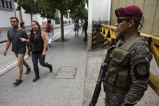 People walk past a Presidential House as soldiers stands guard, one day before the general elections, in the historic district of Guatemala City, Saturday, June 15, 2019. The road to Sunday's presidential election in Guatemala has been a chaotic flurry of court rulings and shenanigans, illegal party-switching and allegations of malfeasance that torpedoed the candidacies of two of the top three candidates.