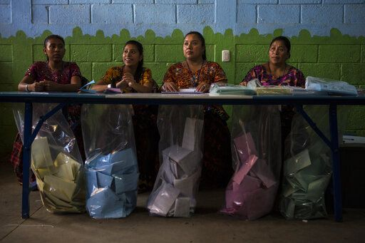 Electoral workers wait for people to cast their votes during general elections in Chinautla on the outskirts of Guatemala City, Sunday, June 16, 2019. Guatemalans are voting for their next president in elections plagued by widespread disillusion and distrust, and as thousands of their compatriots flee poverty and gang violence to seek a new life in the United States.