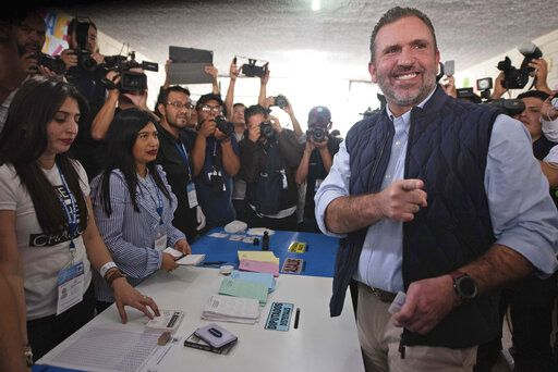 Roberto Arzu, presidential candidate of the PAN and Podemos party coalition, poses for photographers at a polling station during general elections in Guatemala City, Sunday, June 16, 2019. Guatemalans are voting for their next president in elections plagued by widespread disillusion and distrust, and as thousands of their compatriots flee poverty and gang violence to seek a new life in the United States. (AP Photo/Santiago Bill